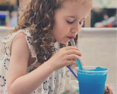 Pige drikker blå Slush Ice