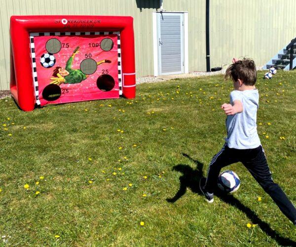 Dreng sparker fodbold efter fodboldmål med skydeskive i lille størrelse